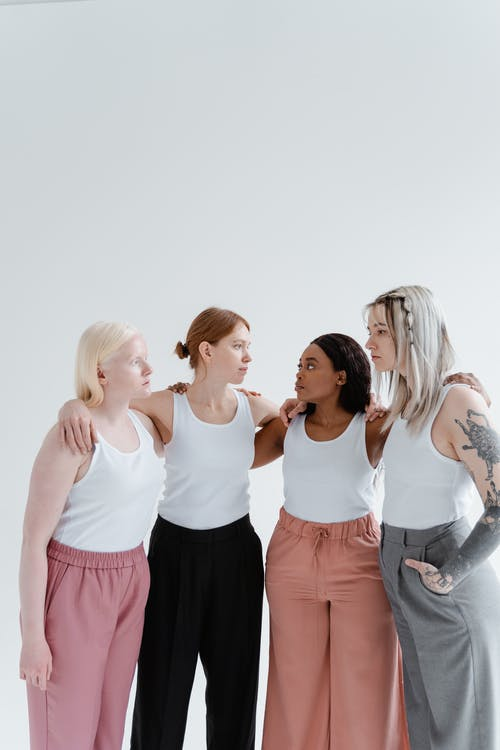 Women in White Tank Top Looking at Each Other
