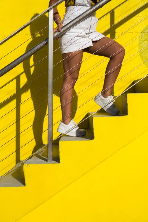 Woman Standing on Yellow Stairs