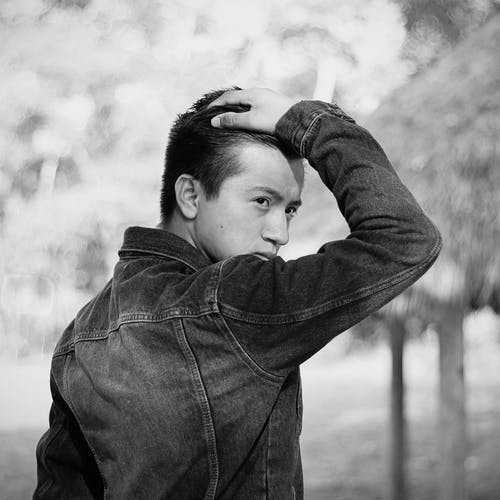 Grayscale Photo of a Man in Denim Jacket Posing