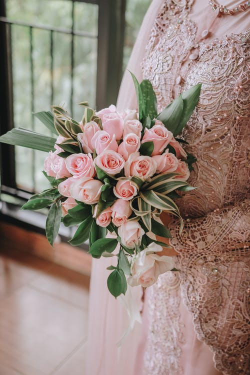 Faceless woman in dress with gentle lace and tender bouquet of fresh roses with pink petals in daytime