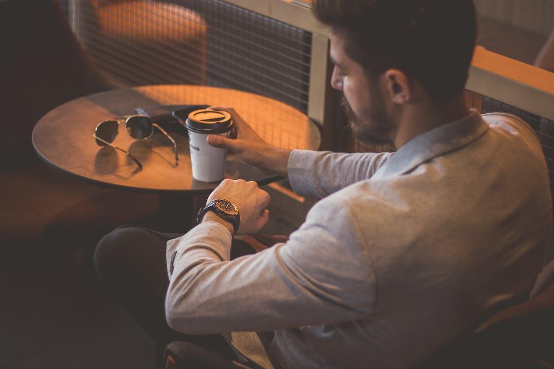 Man in Gray Long Sleeve Shirt and Black Pants Holding White Ceramic Mug