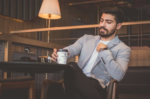 Man in Gray Suit Jacket Holding White Ceramic Mug Sitting on Brown Wooden Chair