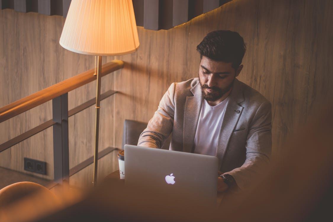 Man in Gray Sweater Using Silver Macbook