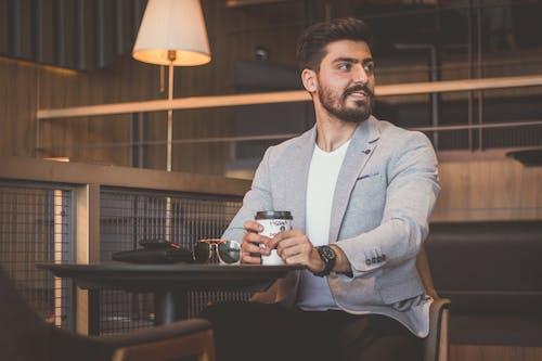 Man in Gray Blazer Holding Black Ceramic Mug