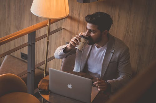 Man in Blue Denim Jacket Sitting on Chair in Front of Macbook