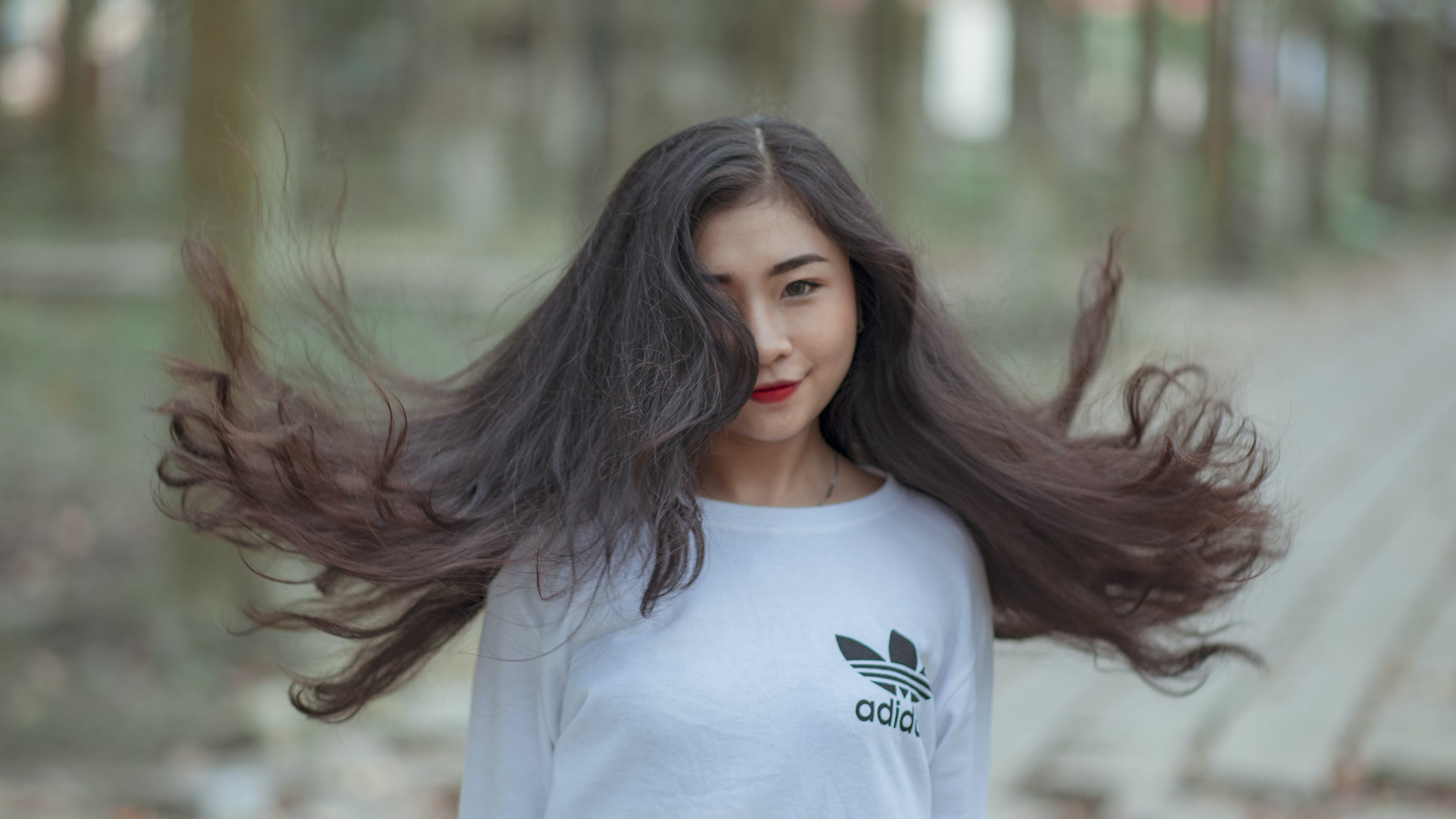 Woman With Long Hair Waving on Air and Wearing White Adidas Shirt