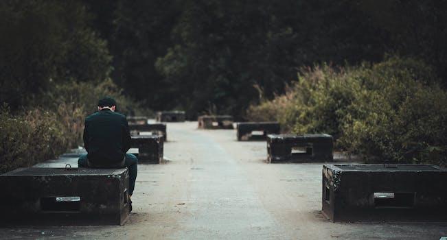 Man in Black Dress Shirt With Blue Denim Shirt Sitting on Black Concrete Bench Near Green Plants