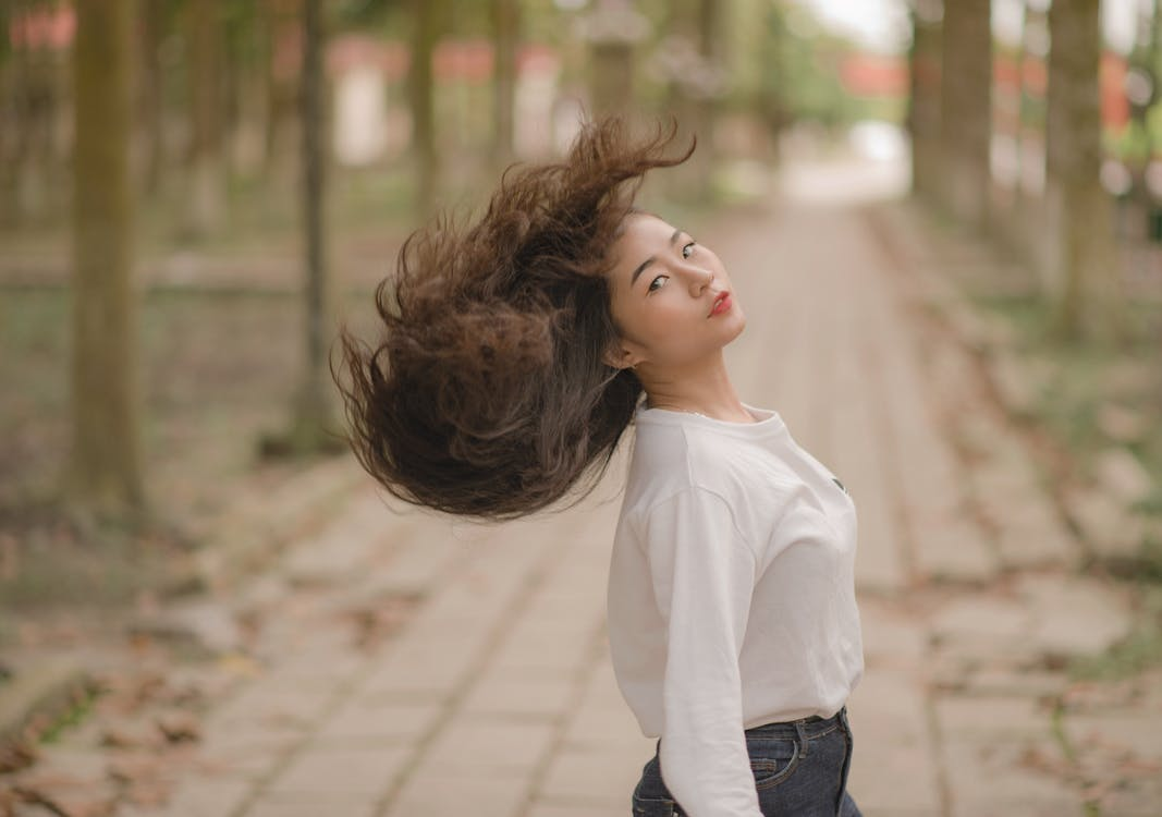 Closeup Photo of Woman in White Crew-neck Long-sleeved Shirt Shaking Her Hair in the Middle on Road