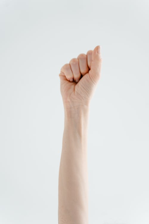 Person's Right Hand Raised with Clenched Fist