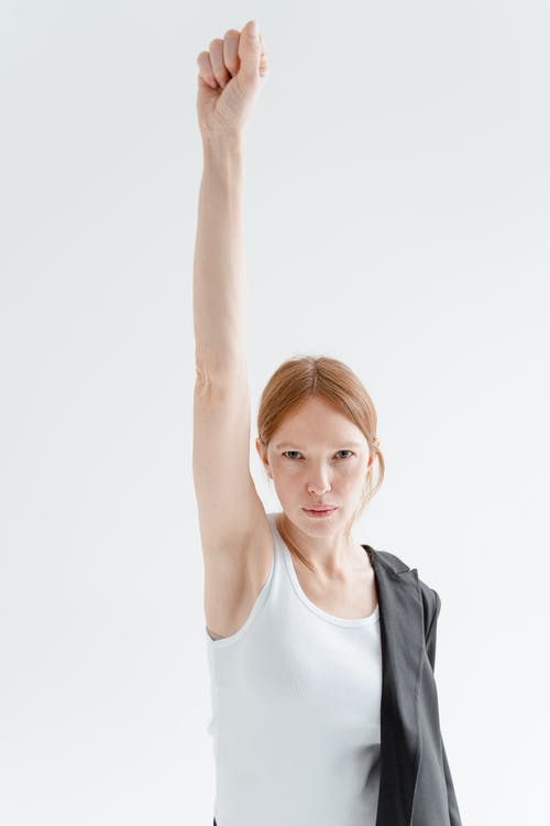Woman in White Tank Top Raising Her Right Hand
