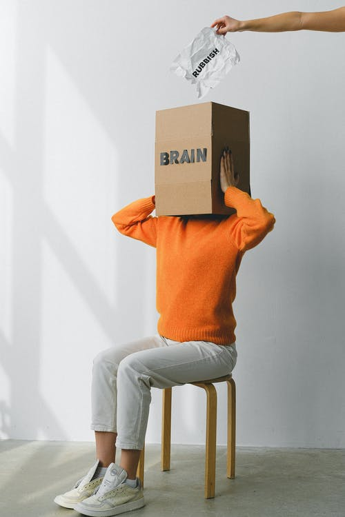 Crop anonymous person putting creased paper with Rubbish inscription in container with Brain title on head of female on chair