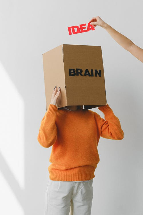 Crop person putting Idea title in cardboard box with Brain inscription on head of female on light background