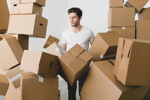 Man between stacks of cardboard boxes at home