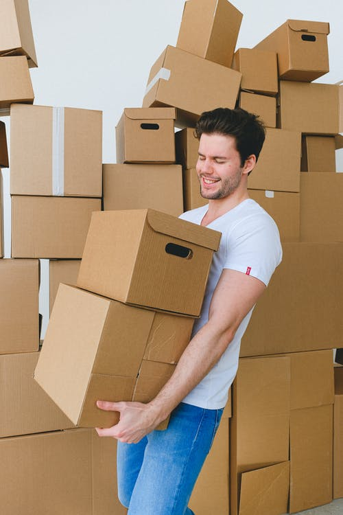 Cheerful bearded male with closed eyes in t shirt and jeans carrying cardboard containers after moving into new house