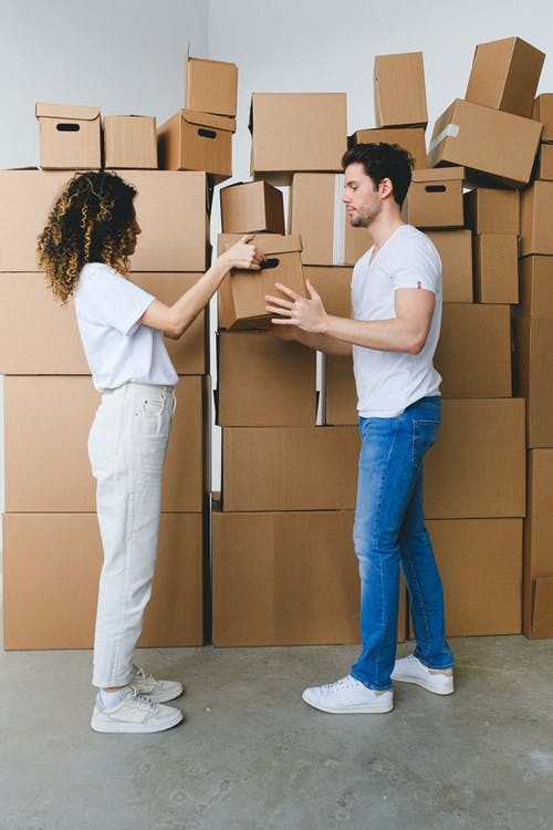 Side view of young lady with curly hair in casual clothes passing cardboard box to boyfriend during moving in new apartment in daylight