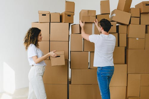 Young couple arranging stack of boxes after relocation