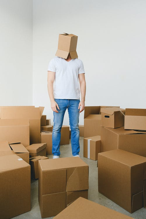 Tired male with carton box on head standing in room before relocation