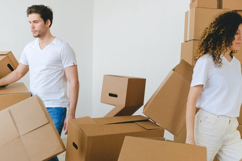 Serious young man and woman in white t shirts carrying carton boxes in light room while moving into new apartment together