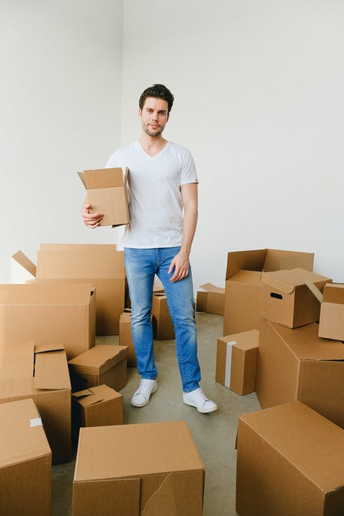 Content relocating man standing amidst boxes and looking at camera