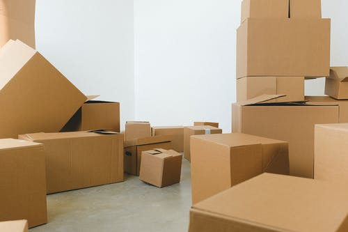 Stack of carton boxes of various shapes and sizes scattered in floor near white walls during relocation