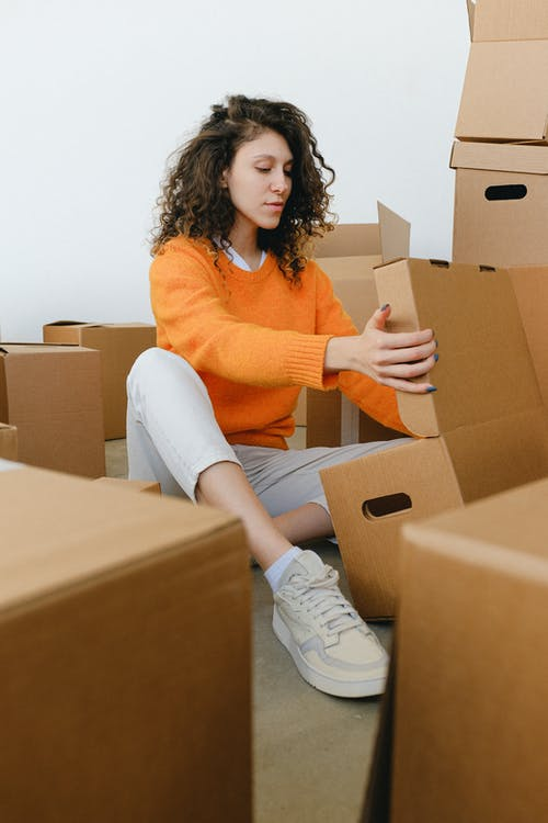 Young woman arranging cardboard boxes during relocation