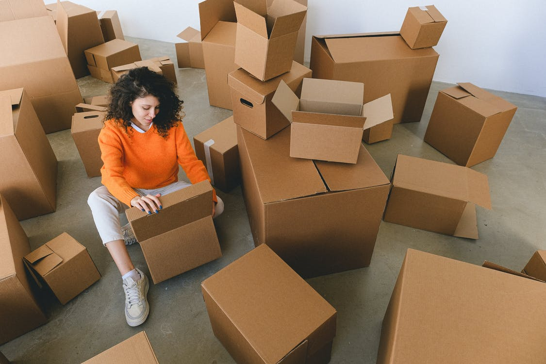 From above of concentrated young female with curly hair in stylish clothes sitting on floor and packing belongings into cardboard boxes before relocation into new apartment