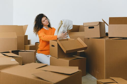 Calm young relocating woman with curly dark hair in stylish sweater packing belongings into pile of cardboard boxes sitting on floor before moving into new apartment
