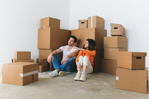 Full body of young happy couple in casual clothes sitting on floor leaning on stack of cardboard boxes and chatting after relocation in new flat
