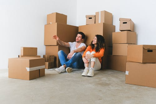 Man and Woman Sitting on Floor Beside Pile of Boxes