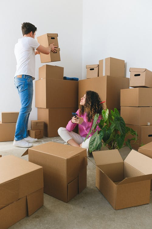 Young lady using smartphone near boyfriend carrying boxes during relocation