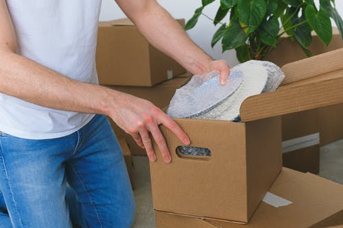 Crop anonymous male in casual clothes packing fragile plates in carton box before moving into new flat in daylight