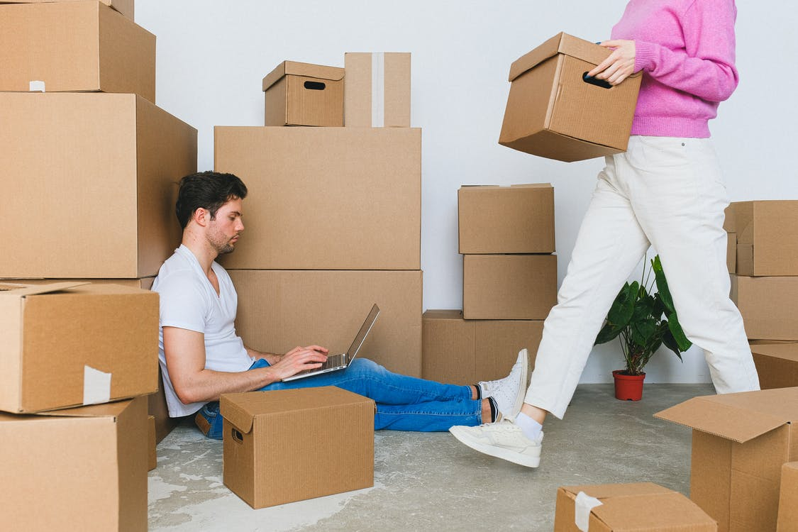 Crop woman arranging carton boxes during relocation with boyfriend using laptop on floor