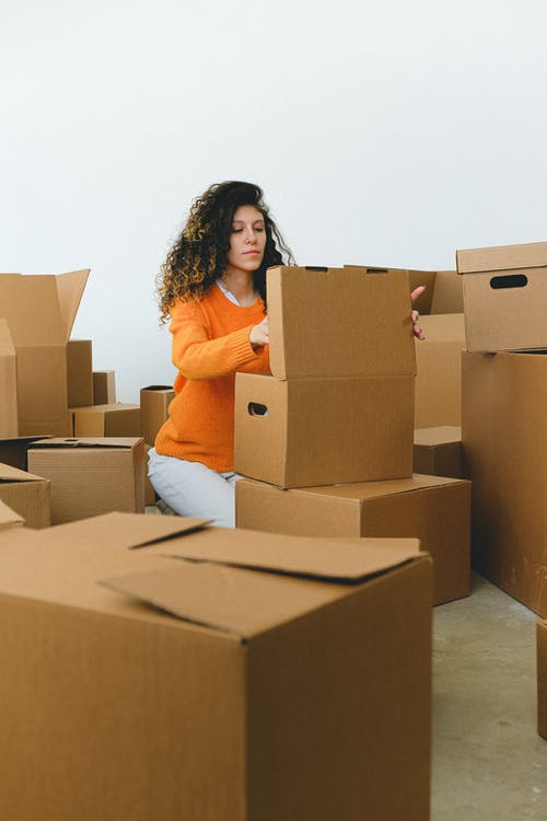 Young relocating lady packing goods into boxes at home