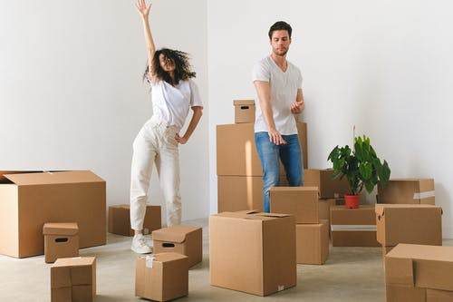 Joyful young couple dancing after moving in new purchased apartment