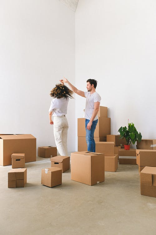 Full body of romantic young couple in casual dancing in new purchased flat amidst pile of carton boxes after relocation