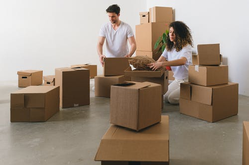Focused young couple packing carton boxes before relocation