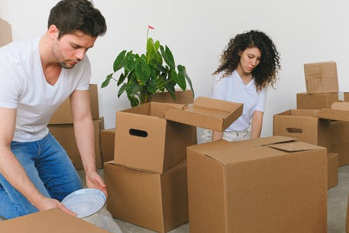 Attentive young couple packing stuff while relocating in new flat