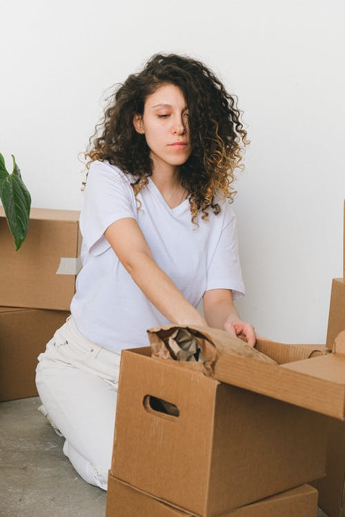 Woman in White T-shirt Sitting on Floor while Holding Brown Cardboard Box