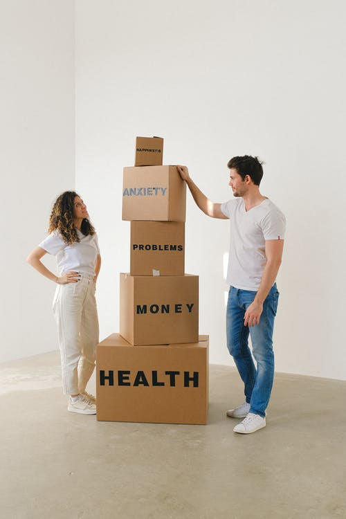 Man and Woman Standing Near Boxes with Labels