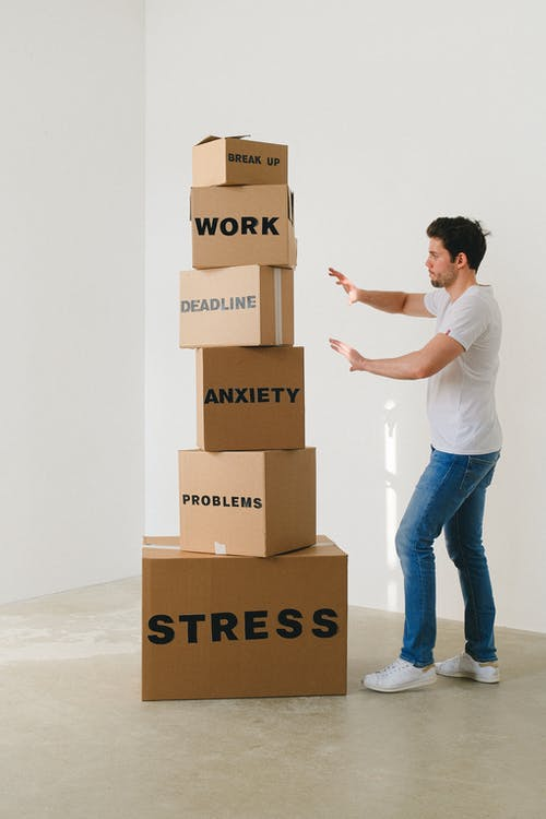 Man near carton boxes with many different words about stress