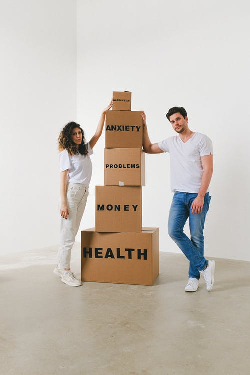 Woman and Man in White Shirt Standing Near Stack of Boxes