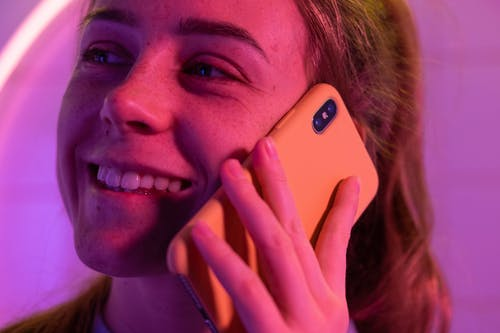 Crop happy female smiling and speaking on mobile phone while looking away in ultraviolet light on blurred background