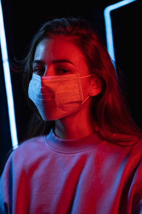 Calm young female in medical mask and sweatshirt looking at camera in bright glowing neon light