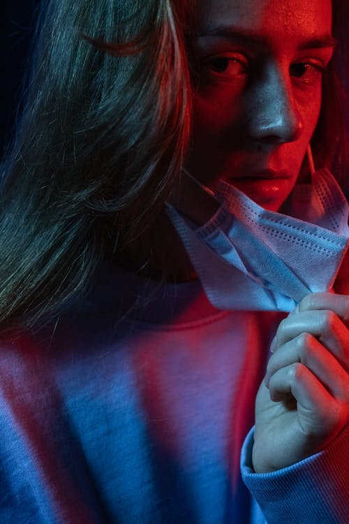 Crop female opening face from protective mask while looking at camera in ultraviolet light