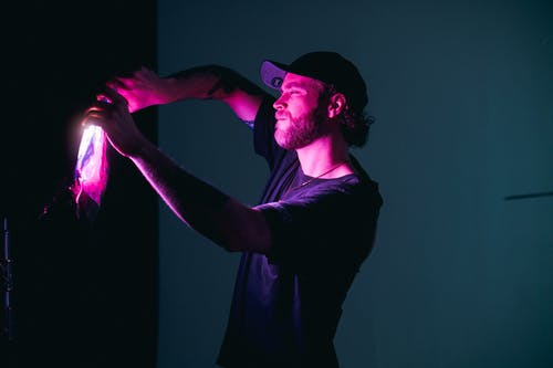 Man in Black T-shirt With Purple Light