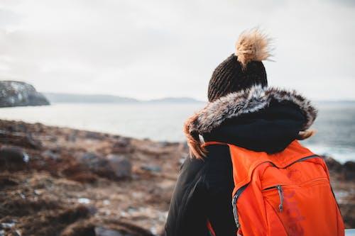 Woman in warm clothes admiring sea