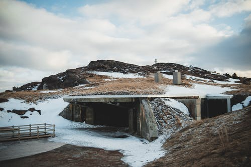Exterior of shabby stone building of mine located in mountainous terrain covered with snow and grass under cloudy sky in winter