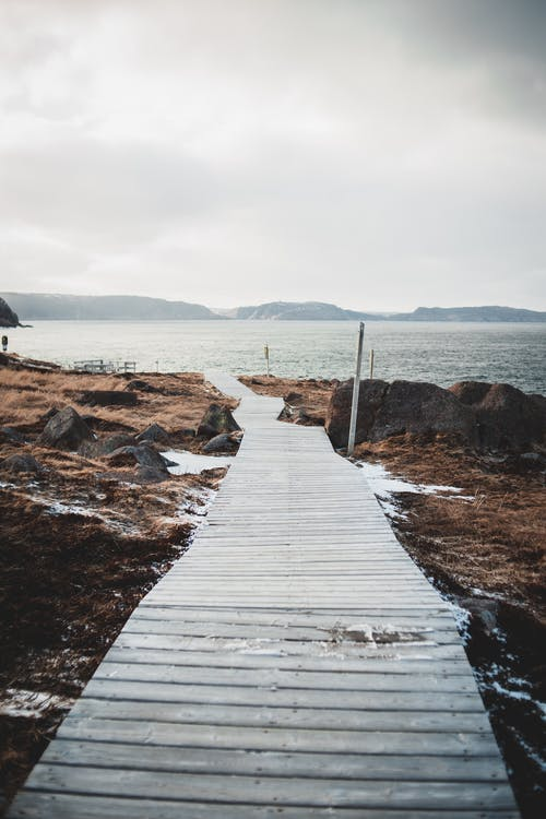 Grassy shore of rippling sea with rocks and empty wooden walkway under cloudy sky on winter day