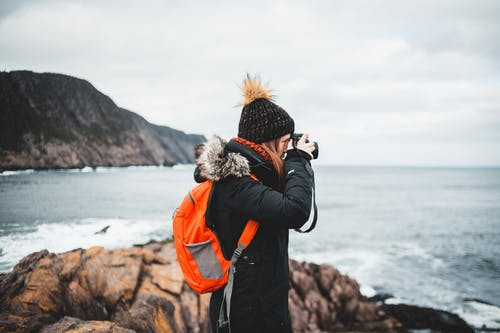 Young woman photographing sea on camera from rocky shore