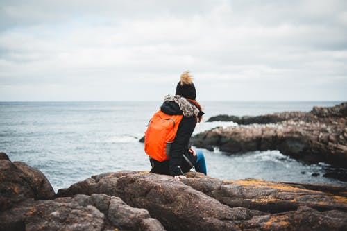 Back view of unrecognizable female traveler in warm clothes and backpack resting on rough rocky cliff and admiring stormy sea under cloudy sky